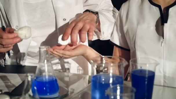 két technikus végeznek vizsgálatokat, a vegyi anyagok és folyadékok kémcsövekbe a kórházban. Kísérletek, a kémia laborban. Közeli kép: