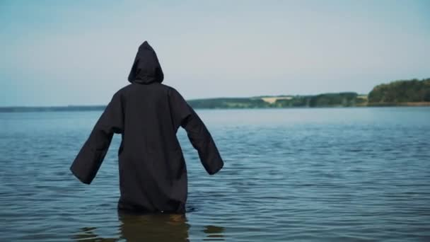 Figura spaventosa in mantello nero nel fiume. Misticismo di Halloween. Costume di Halloween.