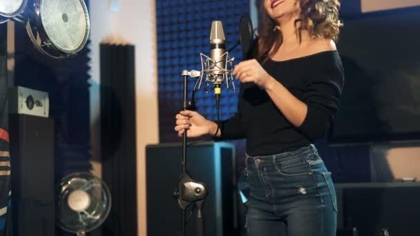 Fiatal gyönyörű barna nő felvétel hang, a dal vagy album professzionális stúdióban. Lány énekel a mikrofon felvétel szoba természetes fényben. 4k