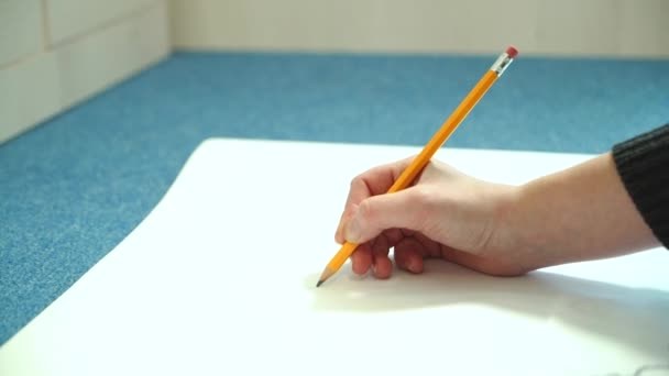 Female hand draws with a pencil. Young woman learns to draw.