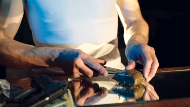 a thug is cutting a package with drugs on the table by knife. Drug trafficking