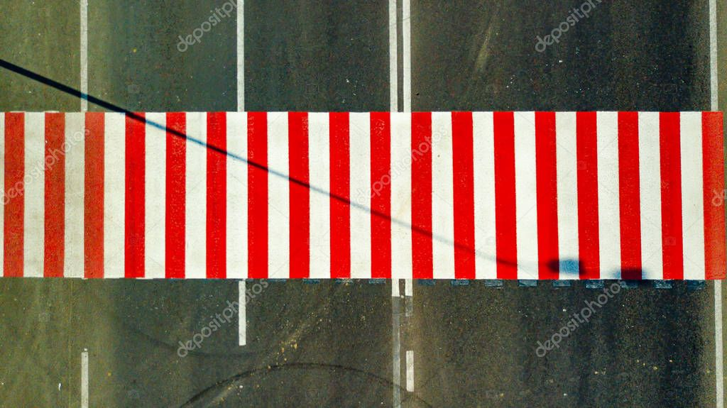 Top view of brightly painted red and white stripes on the road for crossing the street. Pedestrian crosswalk without people. The concept of safety on the road