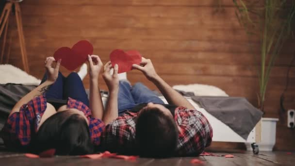 couple in love are playing with handmade hearts in their hands on the bed on St. Valentines Day