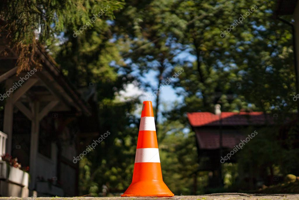 Street cone of two colors with orange and white standing over the natural background. Warning striped plastic orange parking cone near the houses in forest.