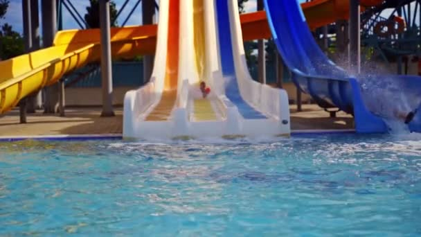 Colorful outdoor water park in summer. Cute boy riding on a slider in the water park. Water splash in the pool. Fun and happiness. Slow motion.