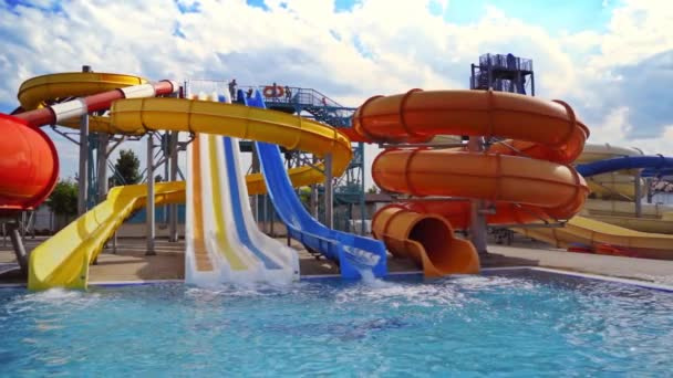 Beautiful aquapark under blue sky. Colorful slides with clear water in the swimming pool outdoors. Joyful entertainment in the open air in a summertime.
