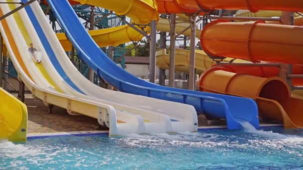 Colorful slides in the outdoor aqua park. Happy boy sliding down from slide into the swimming pool in summer. Slow motion.