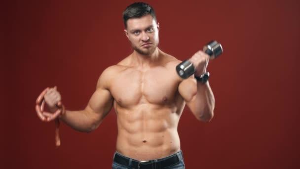 Athletenmännchen mit Hantel und Wurst. Junge Sportler wählen zwischen schwerer Hantel und Wurst. Hemdloser Bodybuilder auf rotem Hintergrund.