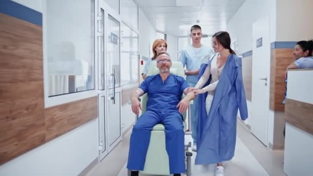Älterer Mann im Rollstuhl. Besucherin, die in der Nähe des kranken Vaters im Rollstuhl durch den Flur geht. Krankenschwester und Arzt zusammen mit Patient auf dem Flur.