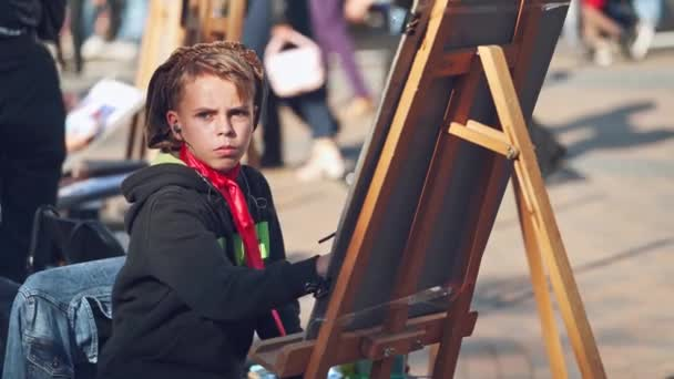 Serious boy is painting on easel in the city. Portrait of a kid artist practices his skills in drawing with brush on the busy city background. City fair.