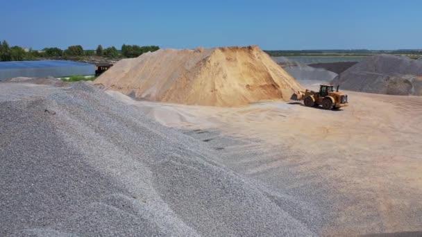 Riesige Haufen Schotter und Sand im Freien. Bulldozer bei der Arbeit auf dem Gelände der Asphaltfabrik an einem sonnigen Tag. Luftaufnahme.