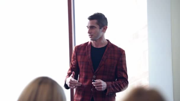 Young businessman talking at conference. Portrait of a manager in jacket explaining something to people. Man conducts meeting indoors.