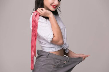 Weight loss concept - slim woman is happy to show her big old trousers.Thin woman in big pants - weight loss concepts