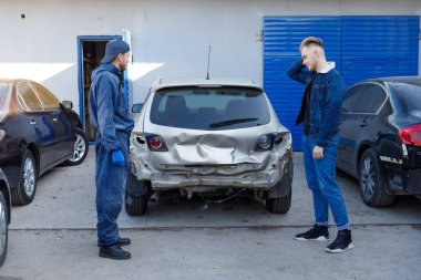 The driver after the accident, emotions, holding his head, the car is broken, at the service station.