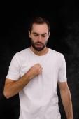 der Typ im weißen T-Shirt vor dem Hintergrund des Rauchs