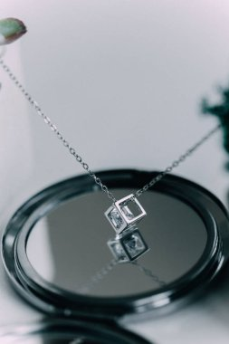 A close-up of a silver chain with a pendant in the shape of a diamond, in the inside of a diamond pebbles, the chain hangs over the mirror. The concept of jewels.