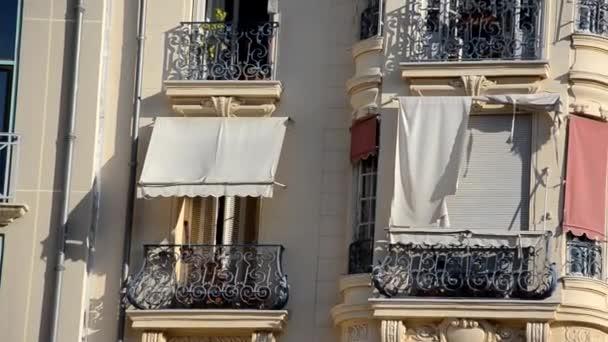 Palmenblätter aus nächster Nähe vor dem Hintergrund eines schönen alten Gebäudes im europäischen Stil Fenster mit Holzfenstern. Haus außen von Palmen umgeben.