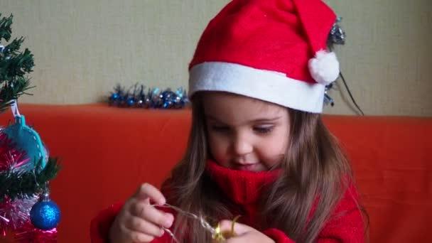 šťastná holčička zdobení vánoční stromeček s krásnými ornamenty a ozdoby těší slavnostní dekorace doma na klidném zimním večeru 4k záběry