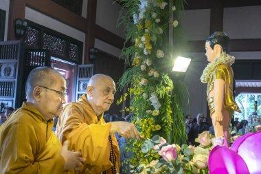 Ho Chi Minh City, Vietnam - May 29, 2018: Group of Vietnamese buddhists monks bath Buddha statue purify body and spirit in Buddha birthday celebration at pagoda in Ho Chi Minh City, Vietnam