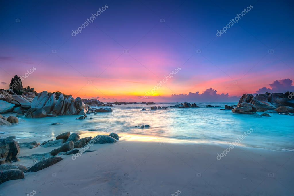 Beautiful sunrise on the beach as the sun rays in the sky purple and below the waves lapping at the shore of the soft great to welcome the new day