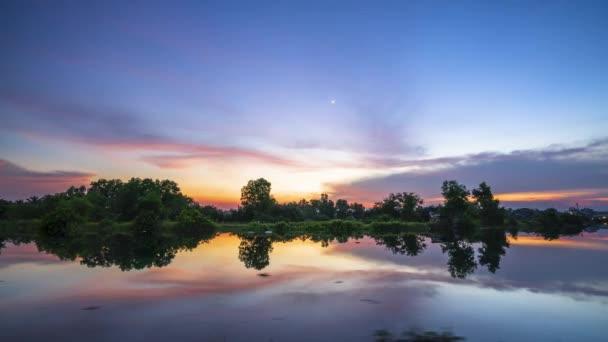 Západ slunce na břehu řeky odráží klidné prostředí na venkově