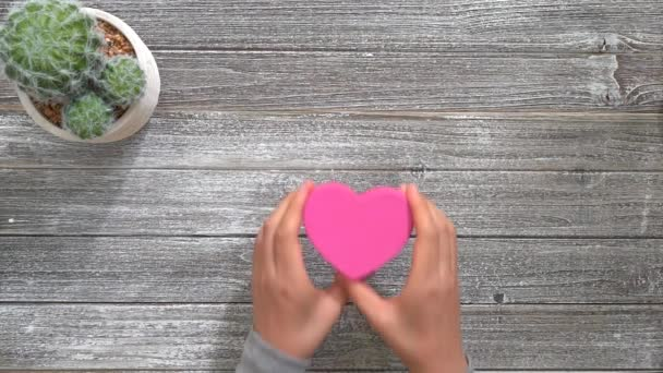 Osoba, která drží růžové tvaru srdce box