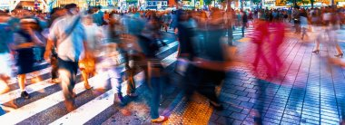People and traffic cross the famous scramble intersection in Shibuya, Tokyo, Japan
