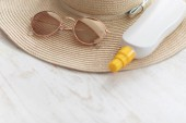 sun protection lotion, sun glasseas and straw hat