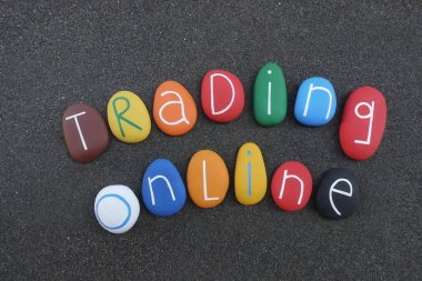 Trading online text composed with multi colored stones over black volcanic sand