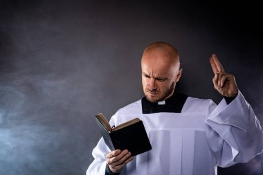 Catholic priest in white surplice and black shirt with cleric collar reading bible and preaching a sermon