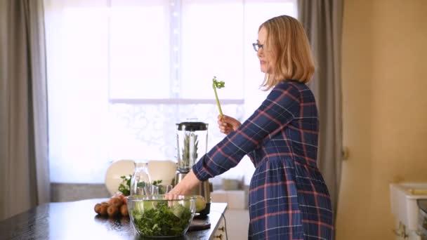 Mladá šťastná žena jíst celer v kuchyni