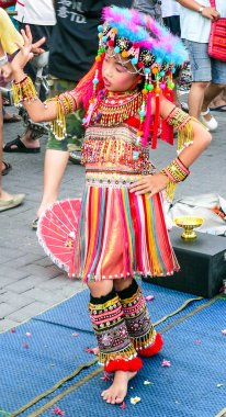 Chiang Mai, Thailand - 22nd July 2007: Young girl in traditional hilltribe dress dancing. She is performing at the Sunday afternoon market,