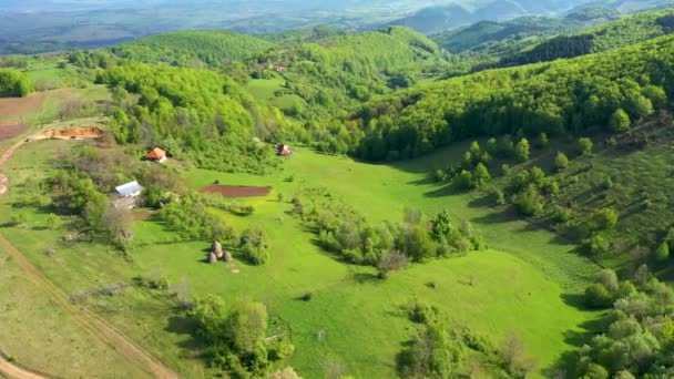 Flying above green countryside hills and village houses, farmland in the spring. Aerial 4k drone view