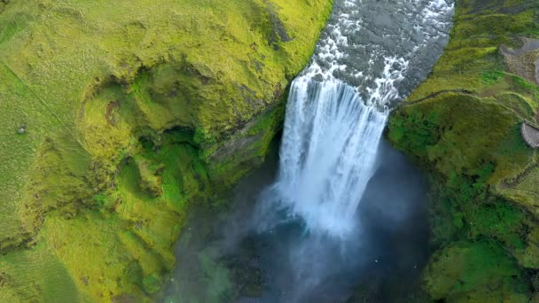 Flying above Skogafoss waterfall in Iceland, aerial drone 4k view. Vibrant green Icelandic landscape