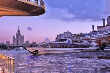 MOSCOW -  DECEMBER 29, 2018: A cruise yacht sails on a frozen water breaking the ice in Moscow city center. Color winter photo.