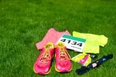 Fényképek Futócipő, marathon rajtszámot (szám), futó hajtómű- és energia gélek fű háttér, a verseny-sport, fitness és egészséges életmód fogalma