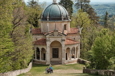 woman taking picture of her family along the path of the historic pilgrimage route from Sacred Mount or Sacro Monte of Varese, Italy