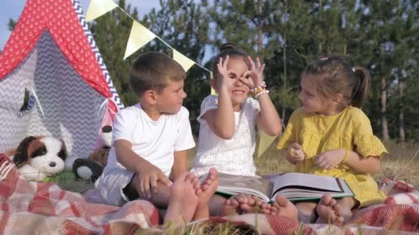 zábavné děti, radostné malé přátele čtou knížku a ukazují si navzájem komické obličeje na pikniku v lese během víkendu v zemi