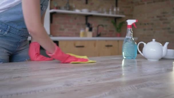 čištění, Žena v rukavicích pracovní stůl s hadříkem a saponátem v kuchyni