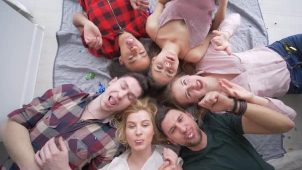 merry beautiful friends blowing bubble gum lying on back together and smile at camera during a home party, top view
