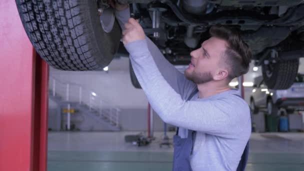 portrét hezkého mechanika ve skafandru na servisním stanovišti pracuje s klíčem pod spodkem auta