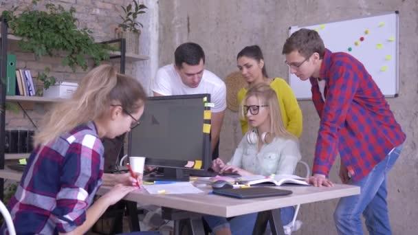 všední den v rušné tvůrčí kanceláři, spolupracovníci stojící u stolu s počítačem a diskutují obchodní nápady