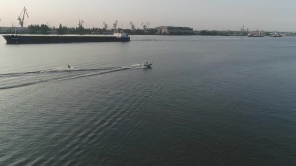 drone view, sportsman in life vest rides on wakeboard along river holding rope tied to powerboat on background of port in slow motion