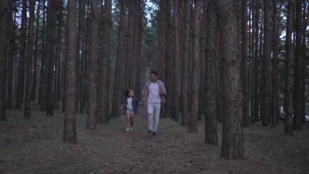 family enjoys weekend in forest, merry father with daughter holding hands running between the rows of pines at evening in slow motion