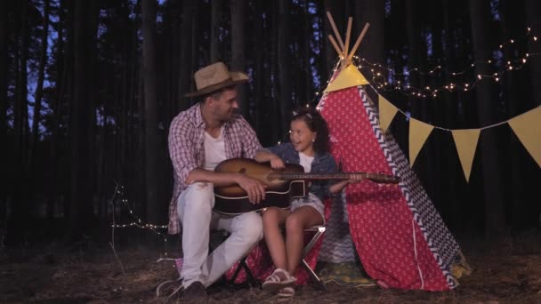 camping in forest, cheerful father and cute daughter sings and play guitar near wigwam decorated with garlands on vacation outdoors