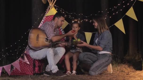 příbuzní na piknik, máma táta a dítě jíst v noci odpočinku v lese proti Wigwam