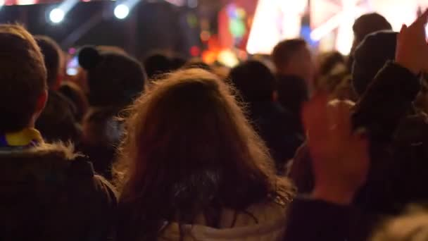 youth dancing in a crowd of people on background of the backlit scene at a street concert in the evening