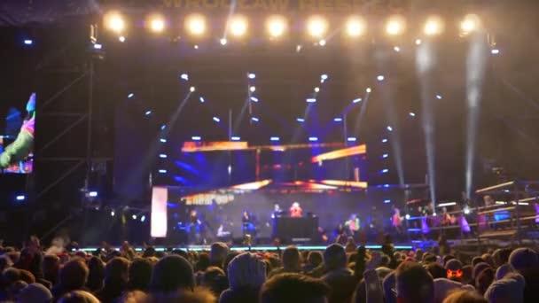 koncert a szabadban, az emberek emelje fel a kezét, hogy egyszerre szemben a háttérben színpadon füst speciális effektek és spotlámpák az esti órákban