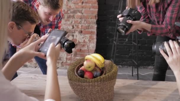 cameramans learn to take pictures of fruits in basket on wooden table use cameras and mobile phone during master class, closeup