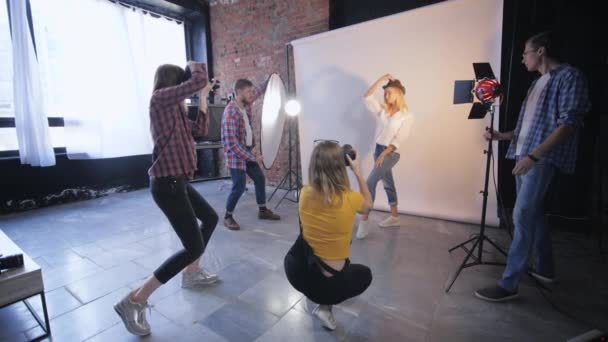 young professionals photographers working in photo studio take pictures beautiful girl model during workshop on photography